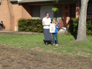 Kerry and daughter showing off Habiturf seed bag at house on corner lot on Shoal Creek